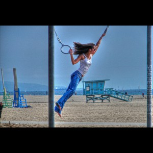 Woman on beach swinging from cables
